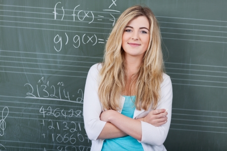 Confident attractive young female student in maths class standing with folded arms in front of the blackboard photo