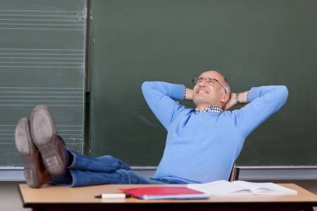 Relaxed thoughtful male professor with hands behind head looking up at desk in classroom photo