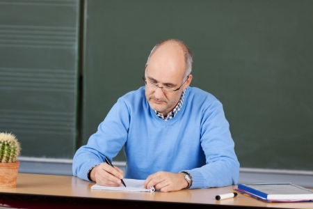 Mature male teacher sitting writing notes at his desk in front of the chalkboard Фото со стока