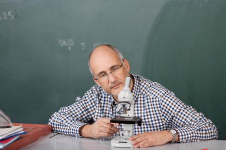 Middle-aged male teacher sitting at his desk in the classroom in front of the blackboard looking at a microscope photo