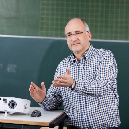 Man professor met projector en muis gebaren in de klas Stockfoto