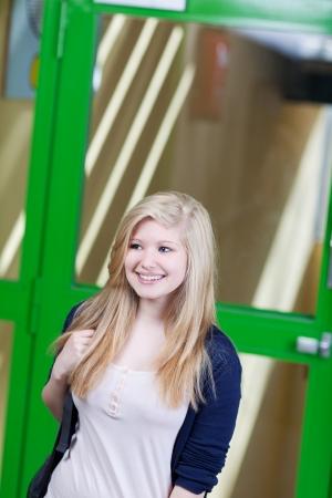 Happy teenage girl walking against door in school photo