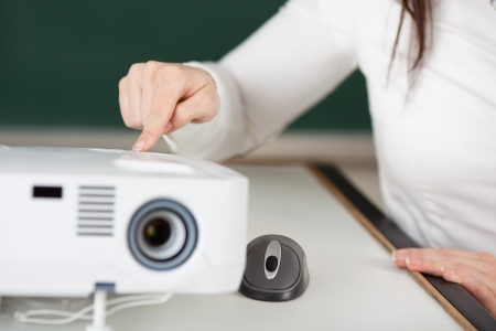 audiovisual: Woman switching on a projector for slides or digital images for a presentation while seated at a small lectern Stock Photo