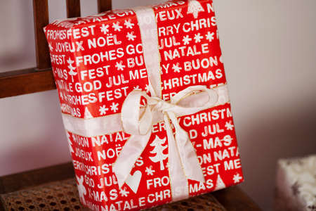 cloesup: Cloesup of a large rectangular red Christmas gift with an Xmas message in white text in various languages printed on the giftwrap Stock Photo