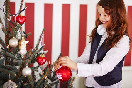 decorating christmas tree: Smiling beautiful young girl standing decorating the Christmas tree hanging colourful red baubles on the branches against a red and white striped wallpaper Stock Photo