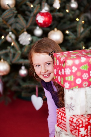 Playful young girl peering around colourful red and white stacked Christmas gifts in front of a decorated Christmas tree photo
