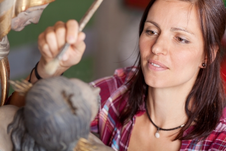 painting: Female artist painting statue with paintbrush in workshop
