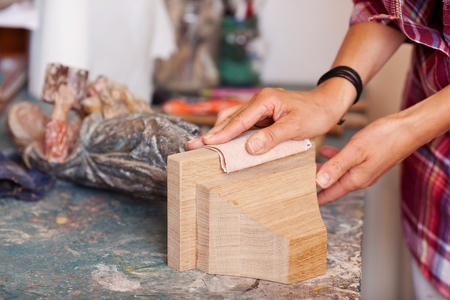 sandpaper: Cropped image of womans hands polishing wood with sandpaper in workshop