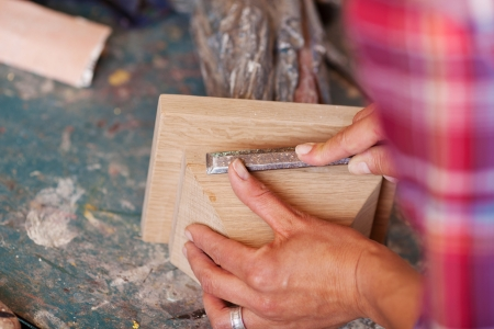 Cropped image of woman carving wood in workshop photo
