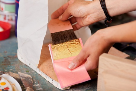 cropped: Cropped image of woman gold leafing in workshop