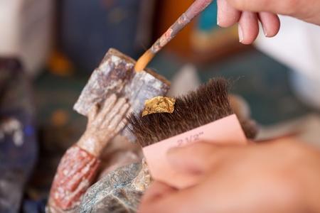 Close-up van de vrouw die met gouden papier op standbeeld in workshop