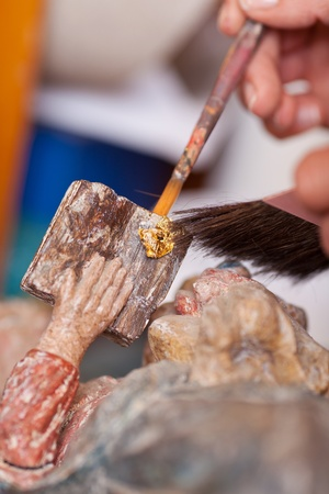 gilding: Closeup of womans hands working on statue in workshop