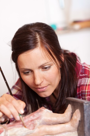 Cropped image of woman using brush on statue in workshop Stock Photo - 21246270
