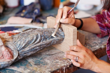 putty: Closeup of woman using putty knife on statue in workshop