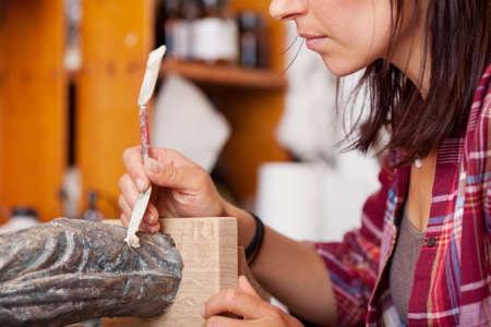 putty: Midsection of woman using putty knife on statue