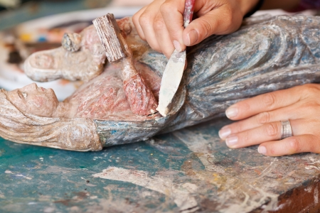 specialized job: Detail shot of woman using putty knife on statue in workshop