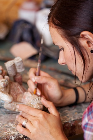 preserving: Woman cleaning statue with brush in workshop