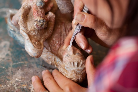 specialized job: Cropped image of woman using scalpel on statue