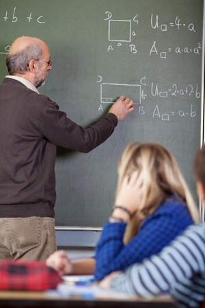 sums: Senior male teacher solving sums on blackboard with students in foreground at classroom Stock Photo