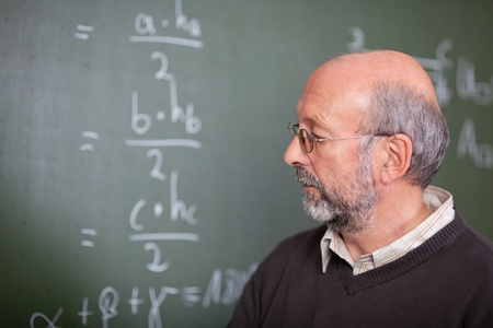 Portrait of teacher standing in front of a blackboard photo