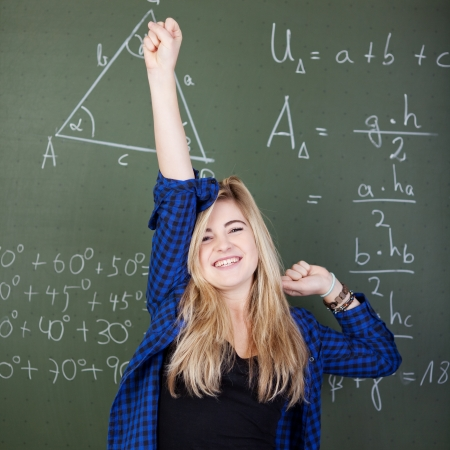 Portrait of happy teenage girl with hand raised celebrating success against blackboard photo
