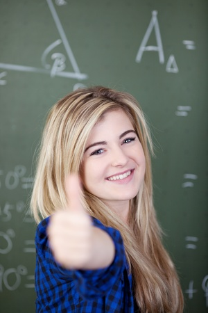 Portrait of confident teenage girl showing thumbsup sign against chalkboard photo