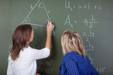Female teacher solving a mathematics question on the blackboard while a female student standing behind and looking. photo