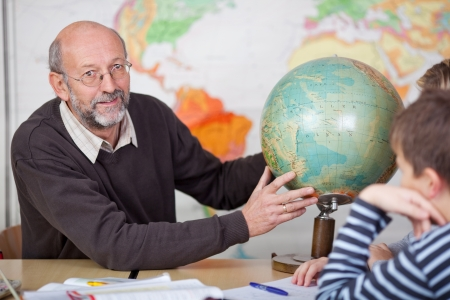An elderly teacher teaching the class of teenagers about geography in school. photo