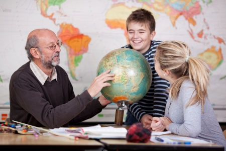 human geography: A young male and female student learning about geography globe in classroom.