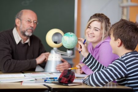 Senior male teacher and students looking at planetarium model at desk in classroom photo