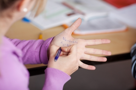 plagiarism: Schoolgirl writing on her hand for cheating in the class tests.