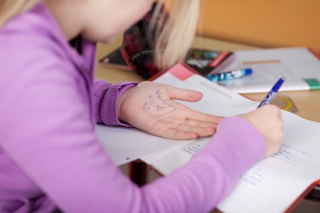 cheat: Midsection of female student copying from cheat sheet on hand at desk Stock Photo