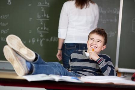 pies masculinos: Feliz estudiante masculino reflexivo con los pies sobre el escritorio, mientras que soñar despierto profesor de pie en el fondo en el aula