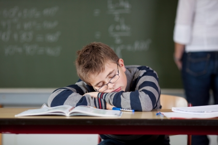 Bored male student sleeping at desk while teacher standing in background photo