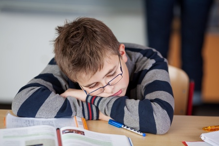Boy student sleeps during lessons in his classroom photo