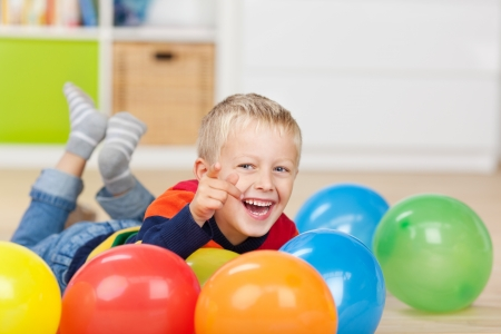 enthusiastic: Portrait of happy little boy pointing while lying with colorful balloons on floor Stock Photo
