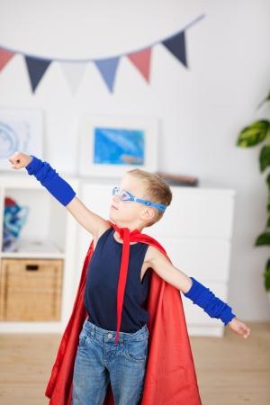 niños actuando: Un superhéroe adorable preescolar, con las manos hacia adelante, cabo soplando mientras vuela por el espacio para llevar a cabo un rescate