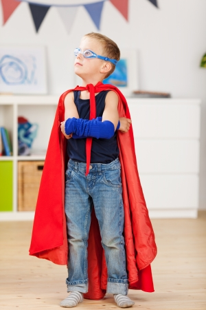 Young boy plays dress-up in the playroom and wears the red cape and mask of a superhero photo