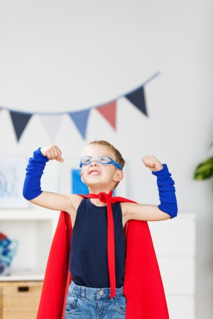 dressing up costume: Strong kid wearing a superhero costume and showing his muscle Stock Photo
