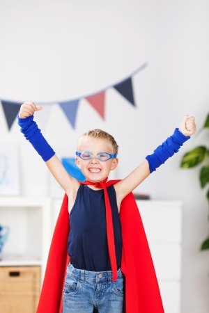 acting: Portrait of happy little boy with arms raised in super hero costume at home Stock Photo