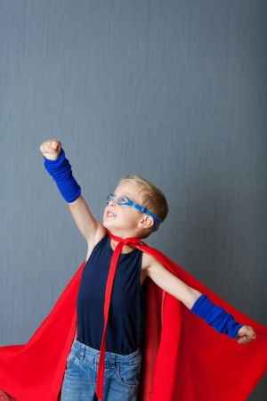 acting: Little boy in super hero costume pretending to fly against blue wall