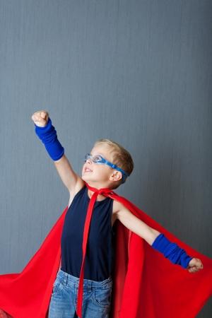 niños actuando: Niño pequeño en traje de superhéroe pretende volar contra la pared azul Foto de archivo