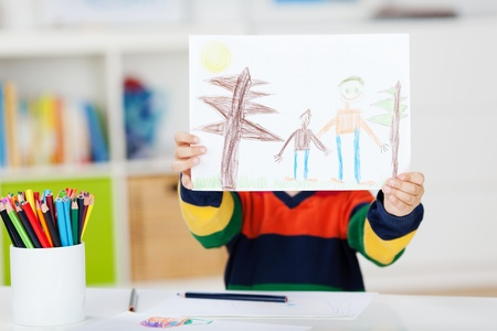 drawing table: Little boy displaying drawing at table in house