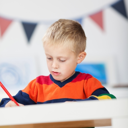 Little boy writing over the blurred background
