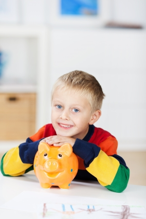 elementary age boys: Portrait of happy little boy with piggybank at table in house