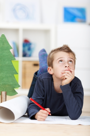 Jonge jongen op de vloer denken aan een tekening begrip Stockfoto