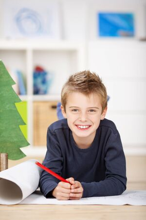 wishlist: Portrait of happy boy drawing on chart paper while lying on floor at home Stock Photo