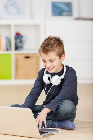 Smiling little boy sitting on the floor and browsing through laptop with headphone photo