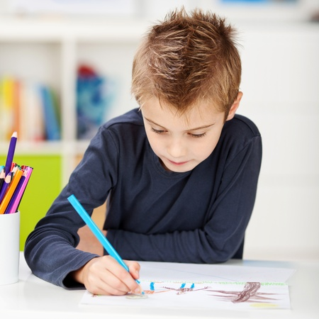 Little boy using colored pencil while drawing on paper at table in house photo