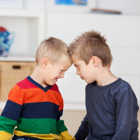 fuming: Angry brothers with head to head looking at each other in house Stock Photo